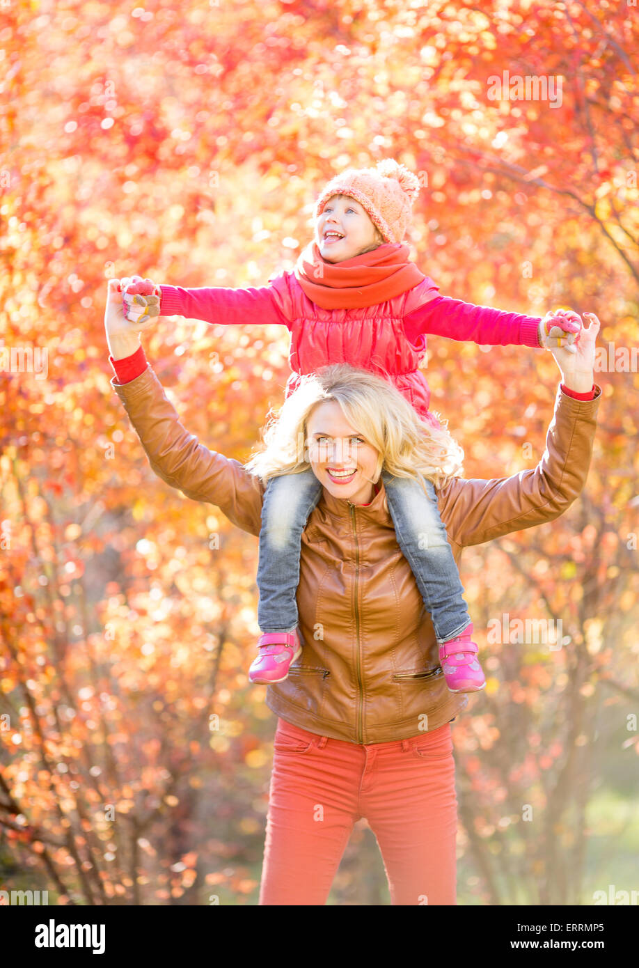 Happy parent and kid walking in fall outdoor - Stock Image