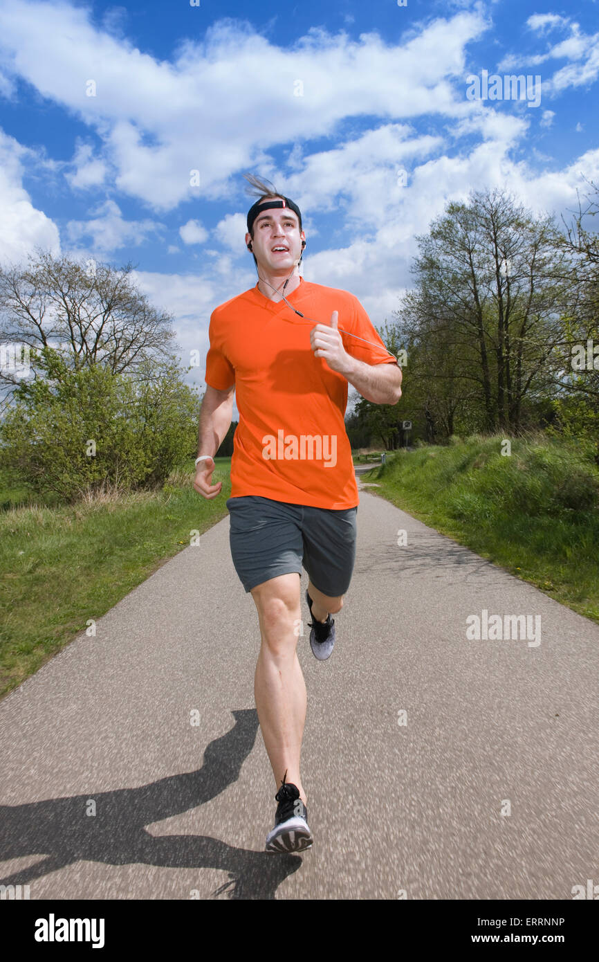 frontal full body view of a young man in the sport dress on asphalt running towards camera - Stock Image