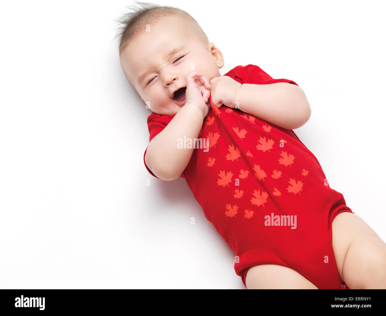 Happy cute yawning four month old baby boy wearing red body suit. Isolated on white background. - Stock Image