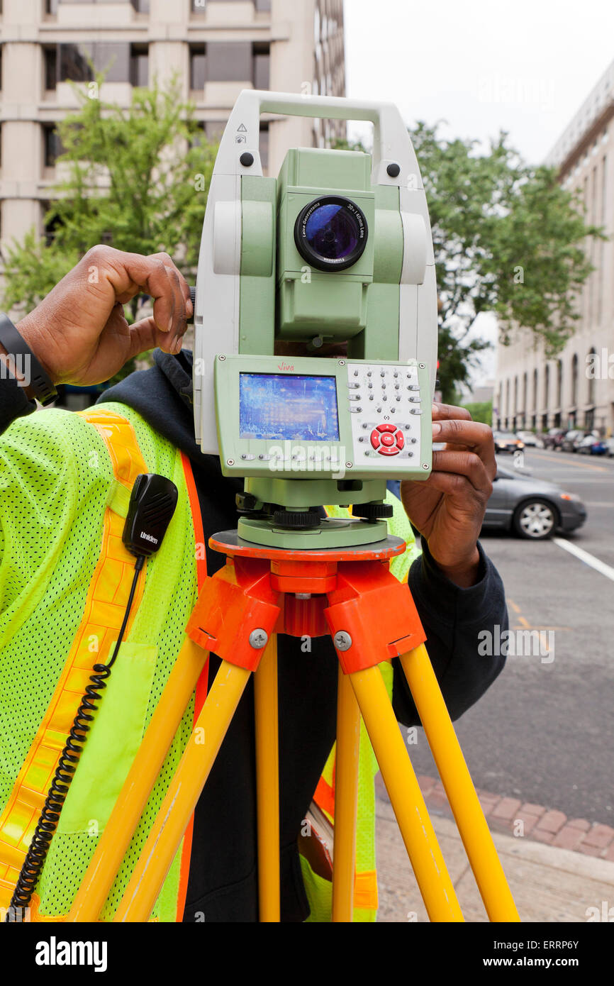 Surveyor using land survey station on tripod - USA - Stock Image