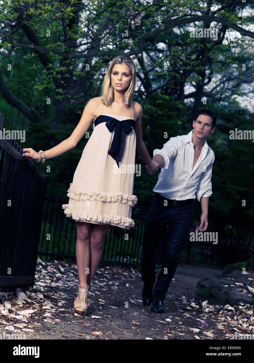 Artistic photo of a young woman leading a man behind holding his hand Stock Photo