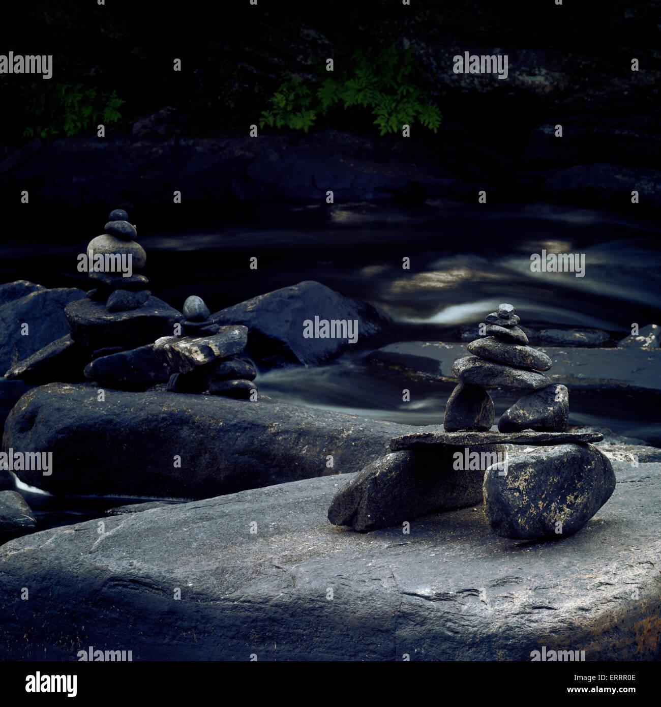 Inuksuk stone figures surrounded by river rapids in Muskoka, Ontario, Canada. - Stock Image