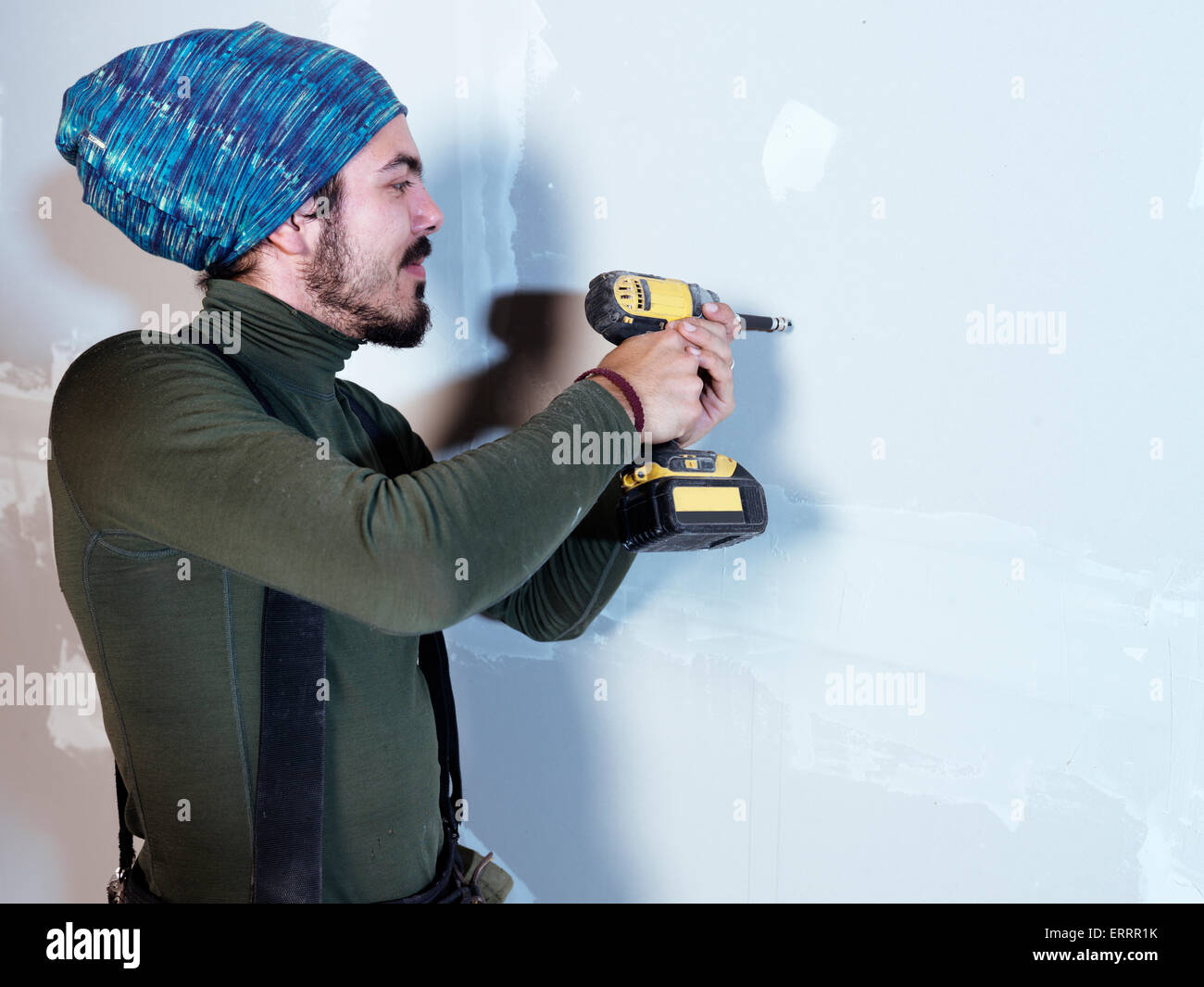 Portrait of a smiling young man contractor worker mounting drywall with a screw gun renovating interior - Stock Image
