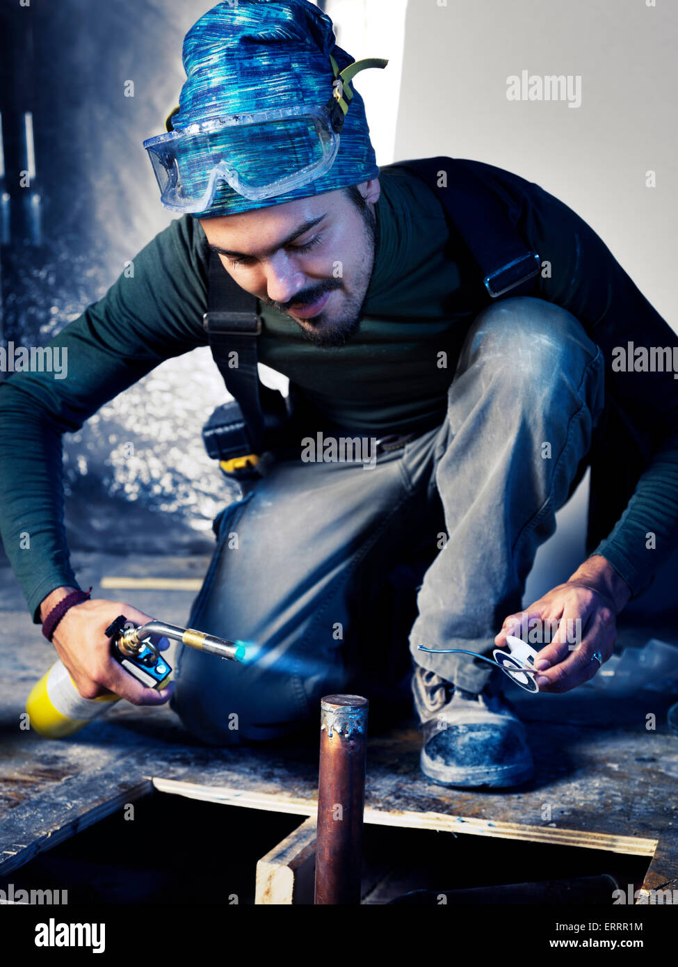 Portrait of man contractor worker with a blow torch capping a pipe doing plumbing - Stock Image