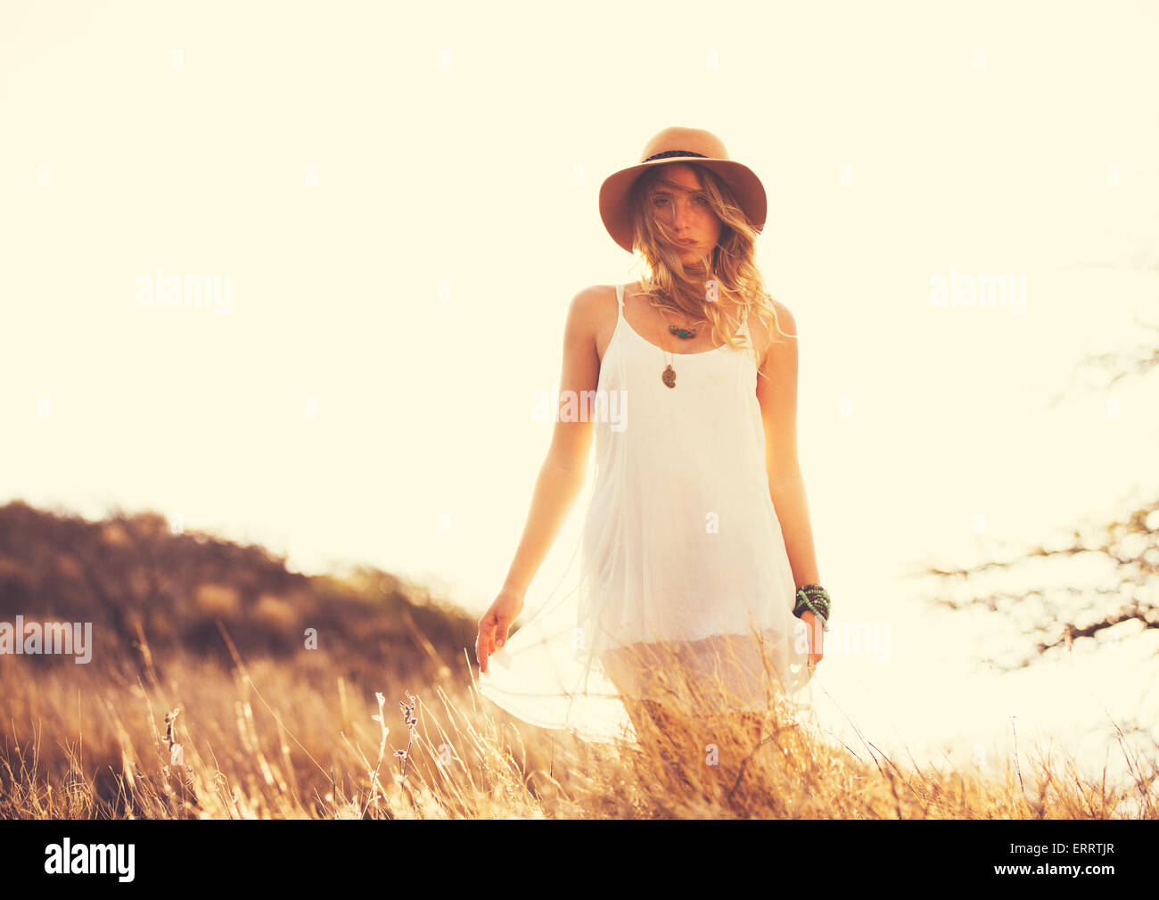 Fashion Lifestyle. Fashion Portrait of Beautiful Young Woman Outdoors. Soft warm vintage color tone. Artsy Bohemian - Stock Image