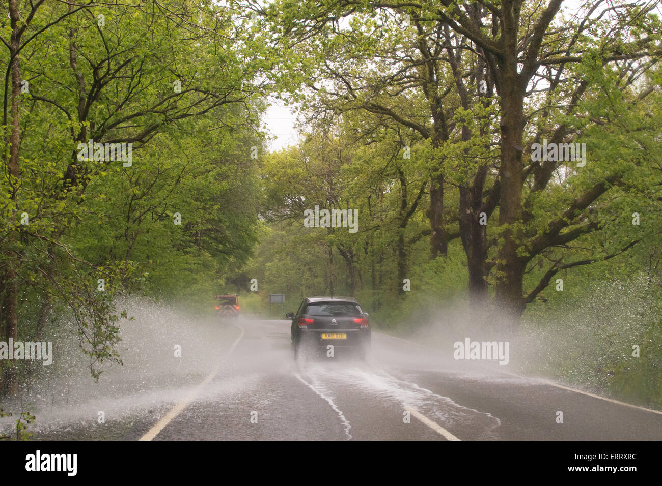 Car splashing through large puddle on country road in Scotland after heavy rain - Stock Image