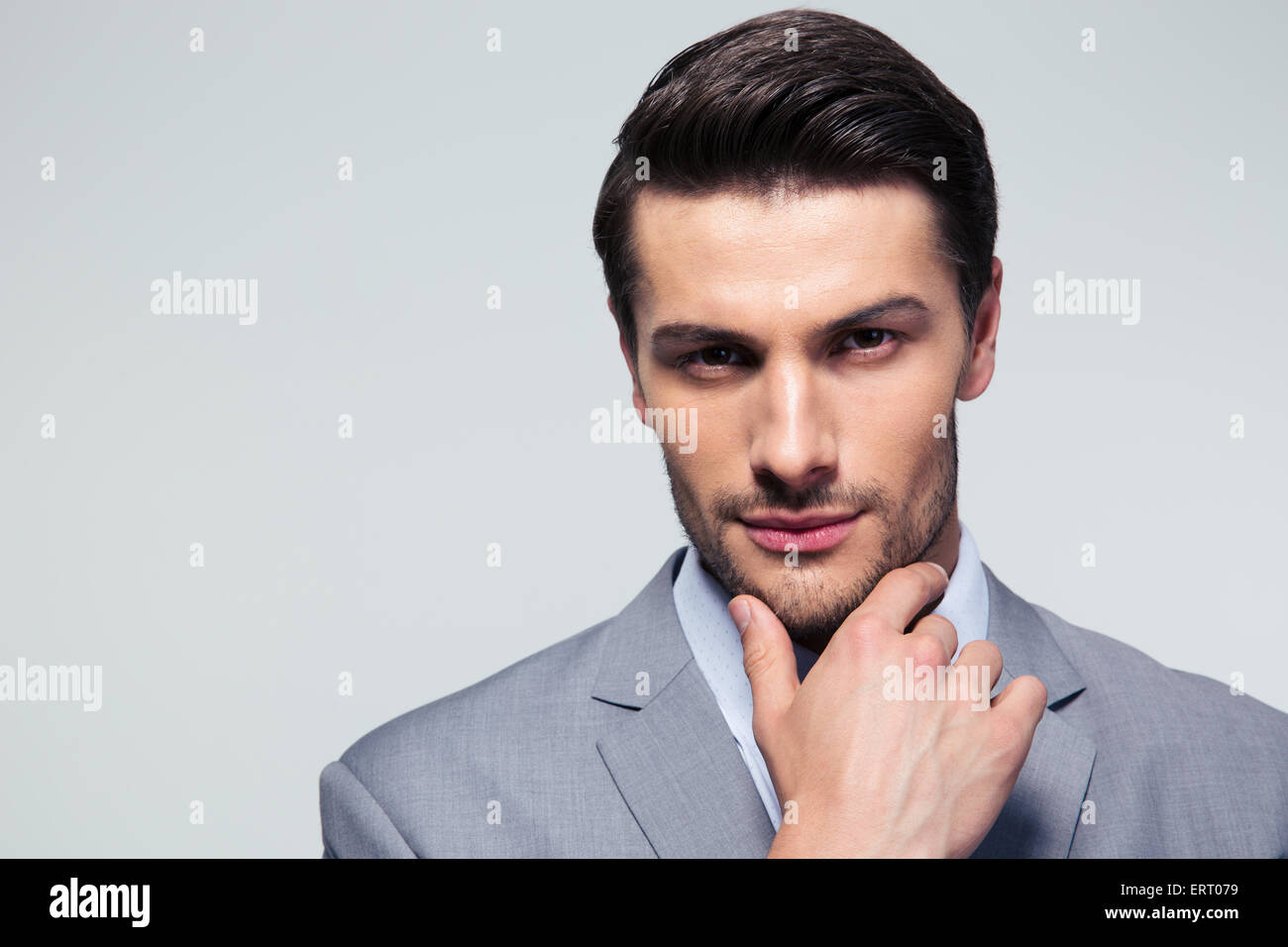 Portrait of a thoughtful businessman touching his chin over gray background - Stock Image