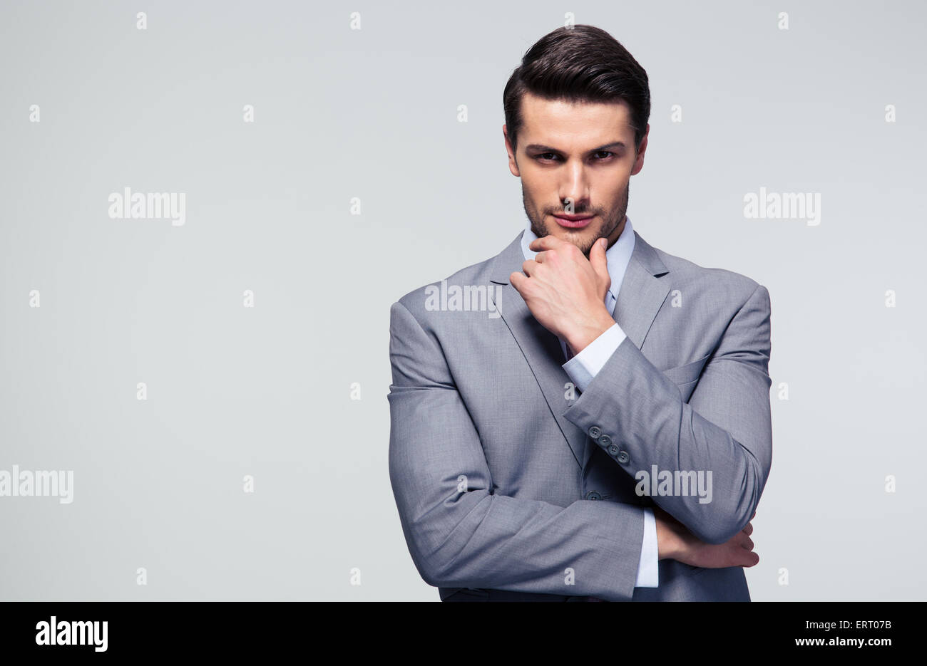 Portrait of a pensive businessman touching his chin over gray background - Stock Image