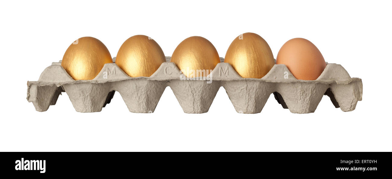 Four golden and one chicken eggs on a tray isolated on white background - Stock Image