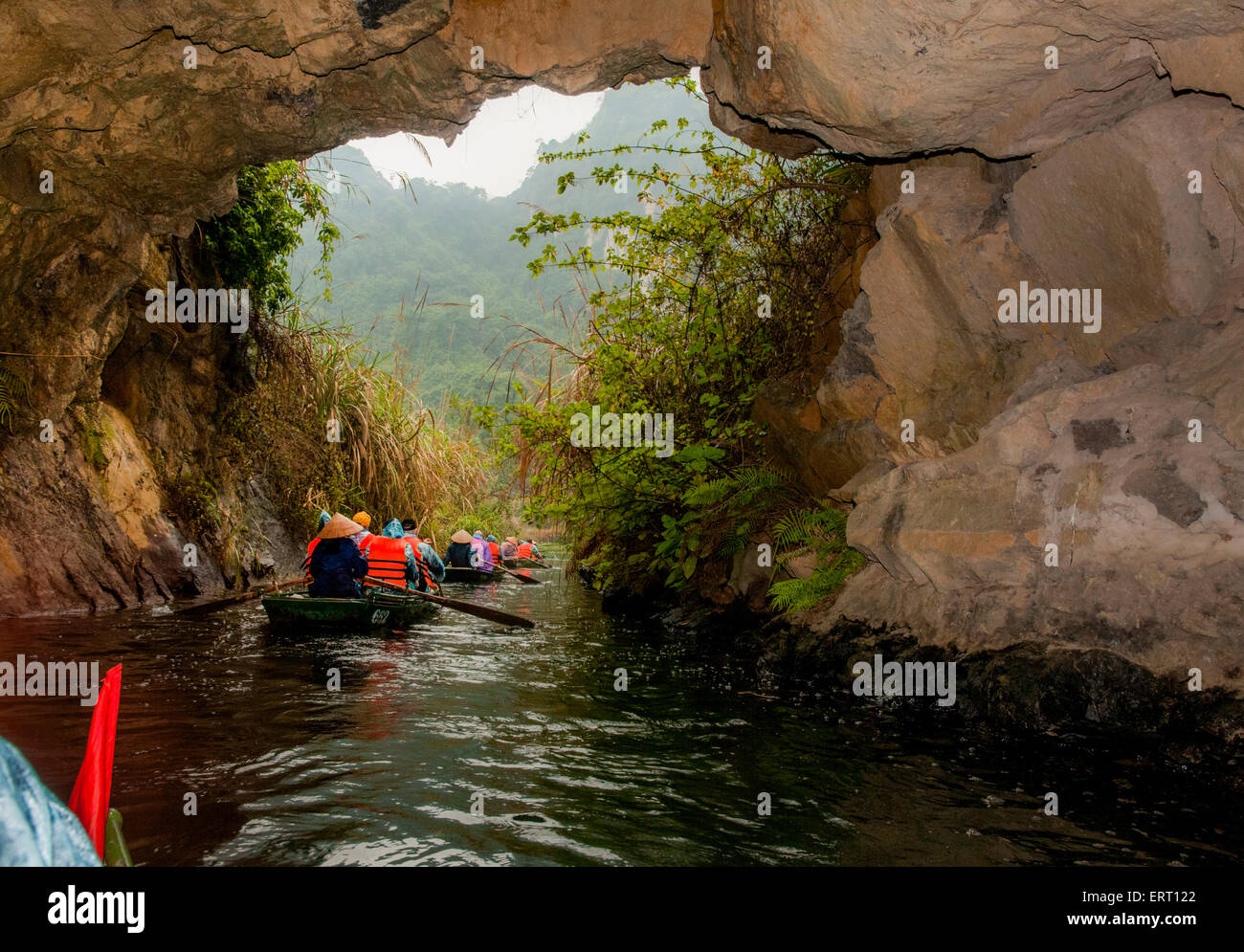 Traveling through Tam Coc caves on the Ngo Gong River in Ninh Binh, Vietnam - Stock Image