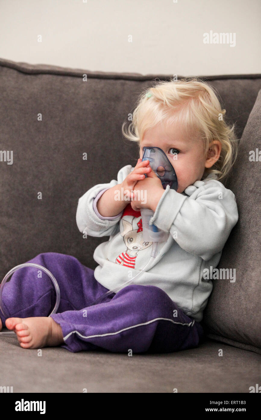 Baby uses an inhalation mask by herself - Stock Image