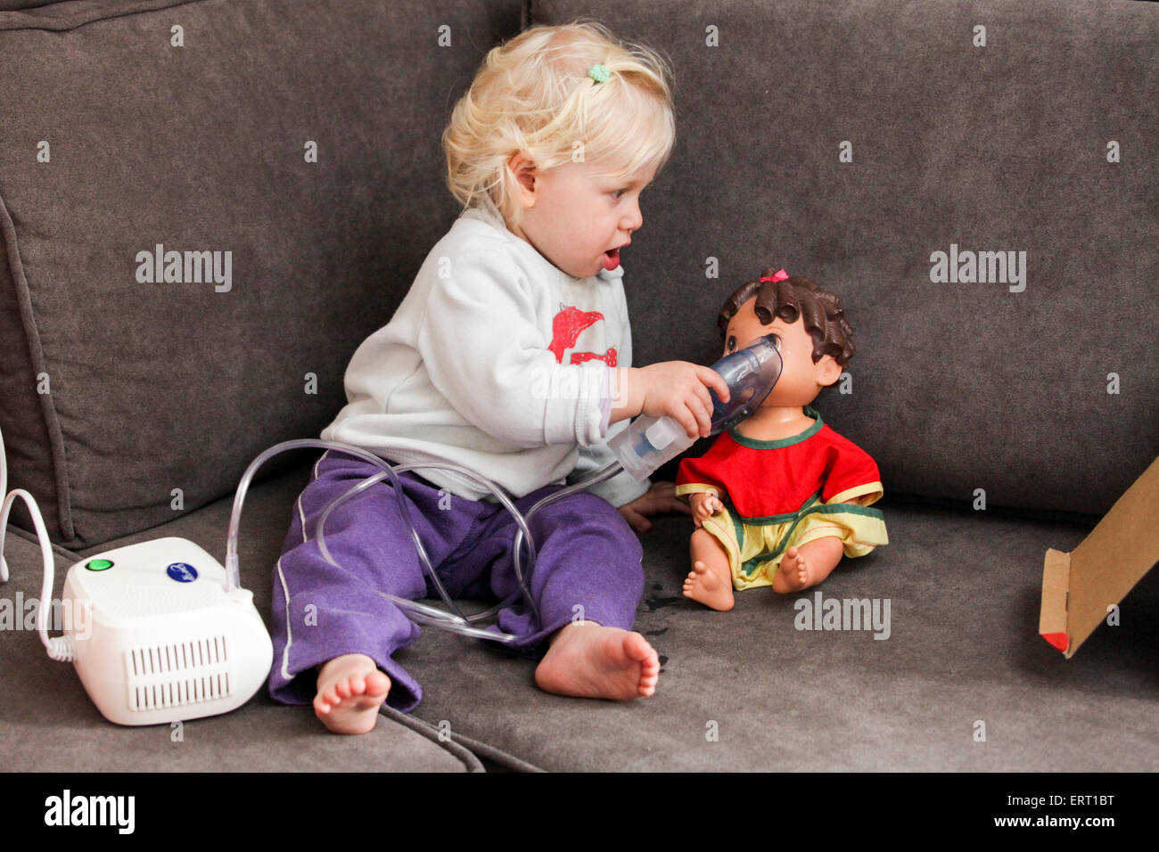 Baby uses her inhalation mask to treat her doll - Stock Image