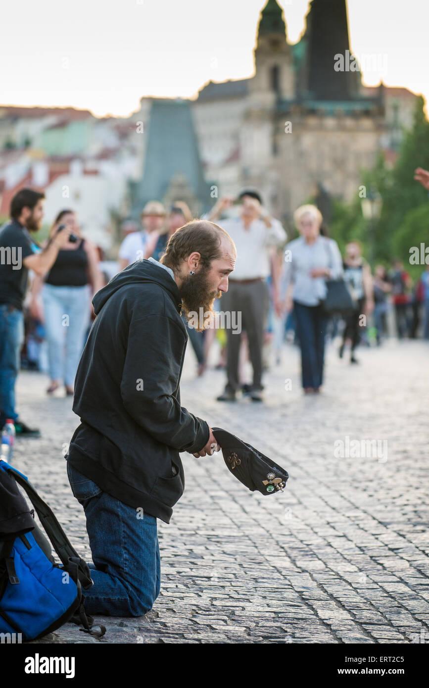 Beggar on Charles Bridge in Prague, Europe - Stock Image