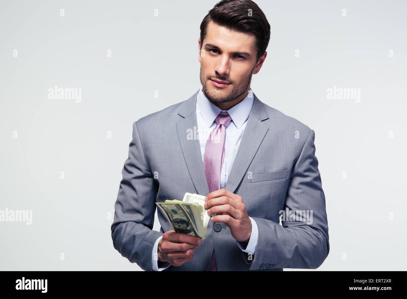 Handsome businessman counting US dollars over gray background and looking at camera - Stock Image