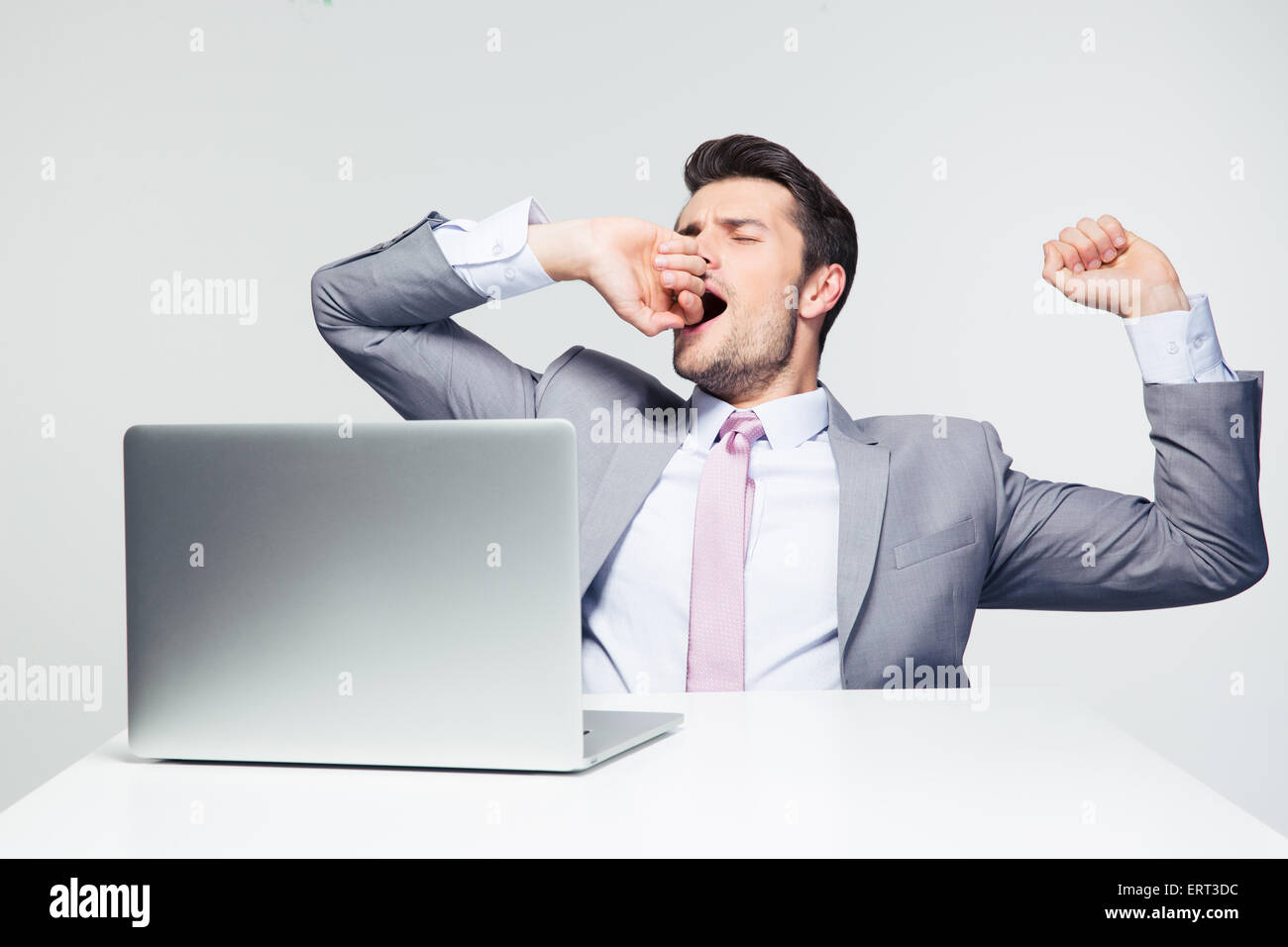 Businessman sitting at the table with laptop and yawning over gray background - Stock Image