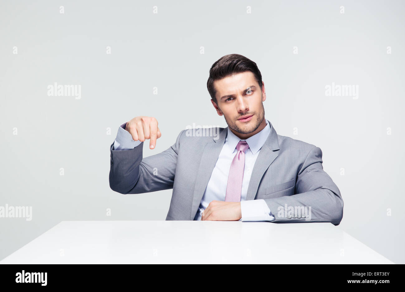 Confident businessman sitting at the table pointing finger down over gray background. Loooking at camera - Stock Image