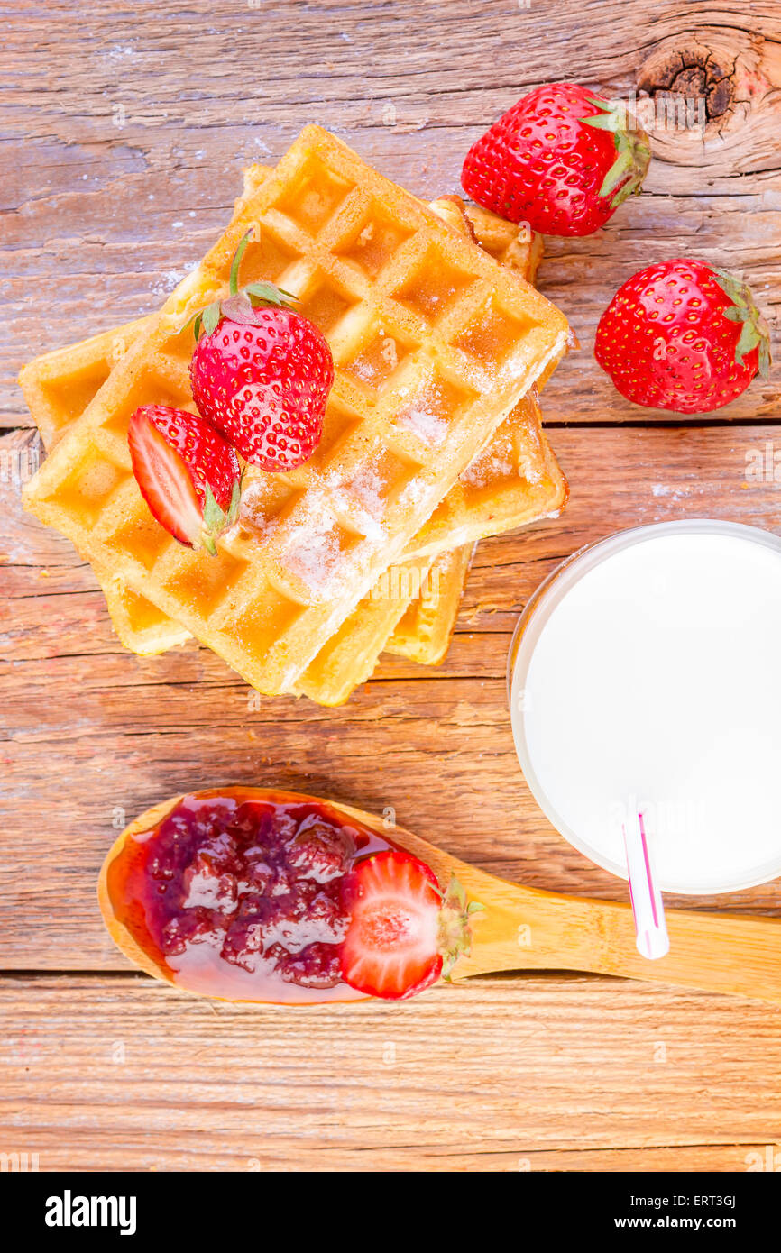 homemade waffles with strawberry jam and glass with milk on wooden background - Stock Image