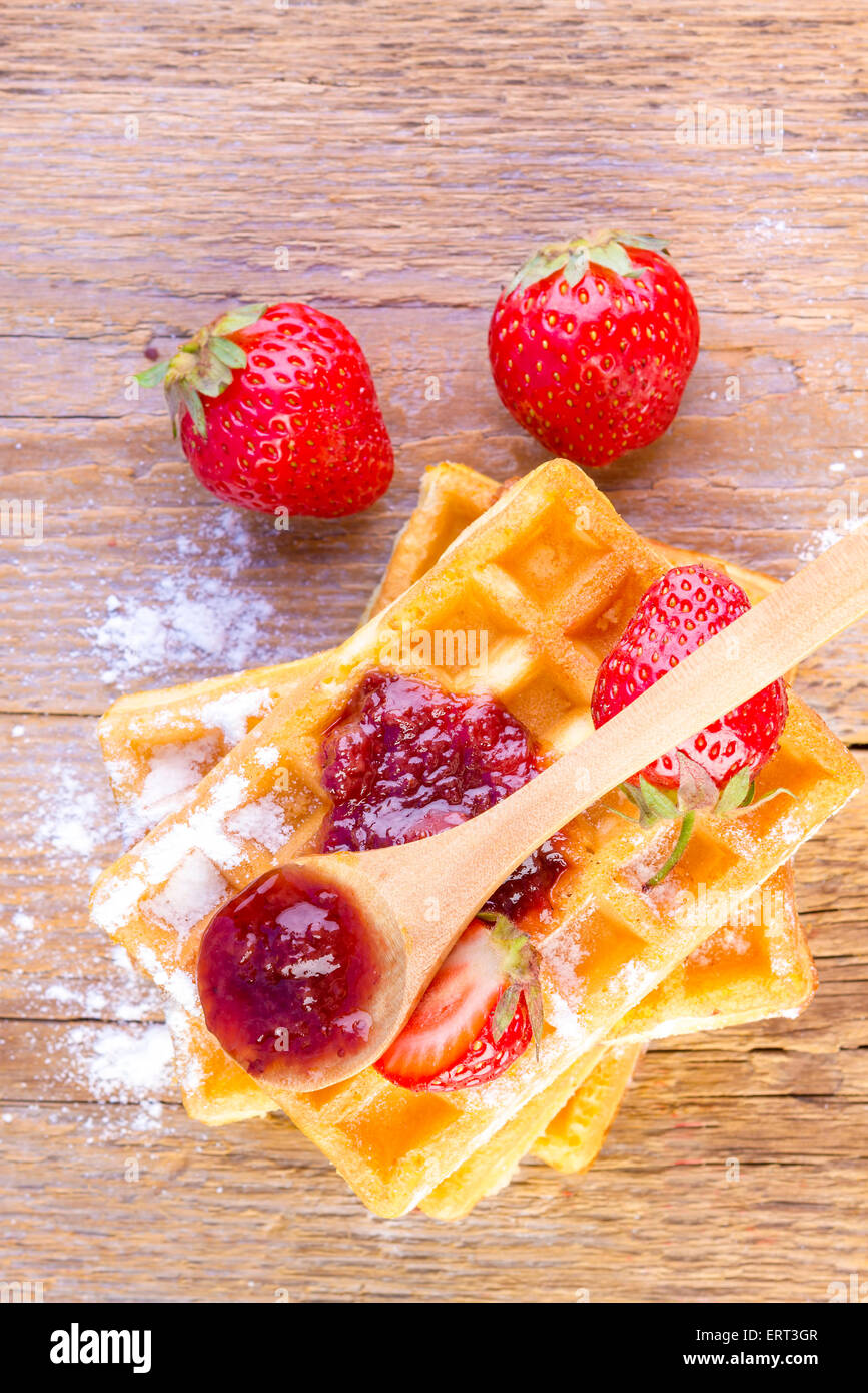 homemade waffles with strawberry jam on wooden background - Stock Image