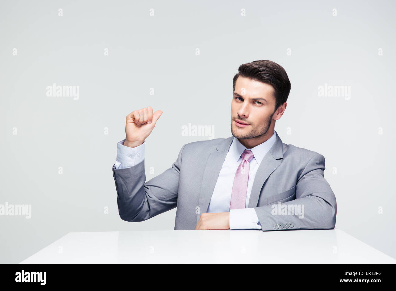 Confident businessman sitting at the table pointing finger back over gray background - Stock Image