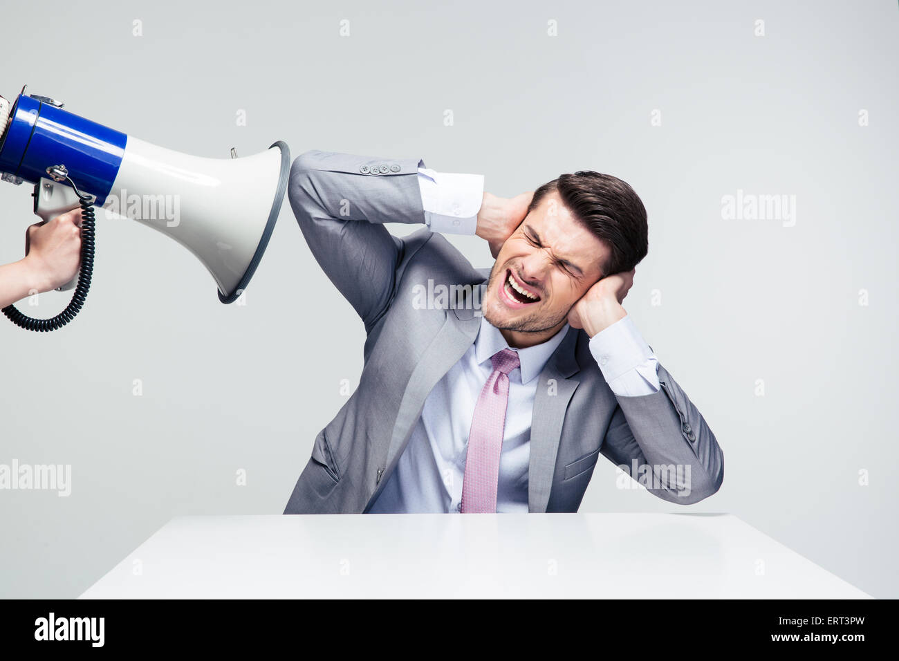 Businessman sitting at the table and covering his ears from megaphone over gray background - Stock Image