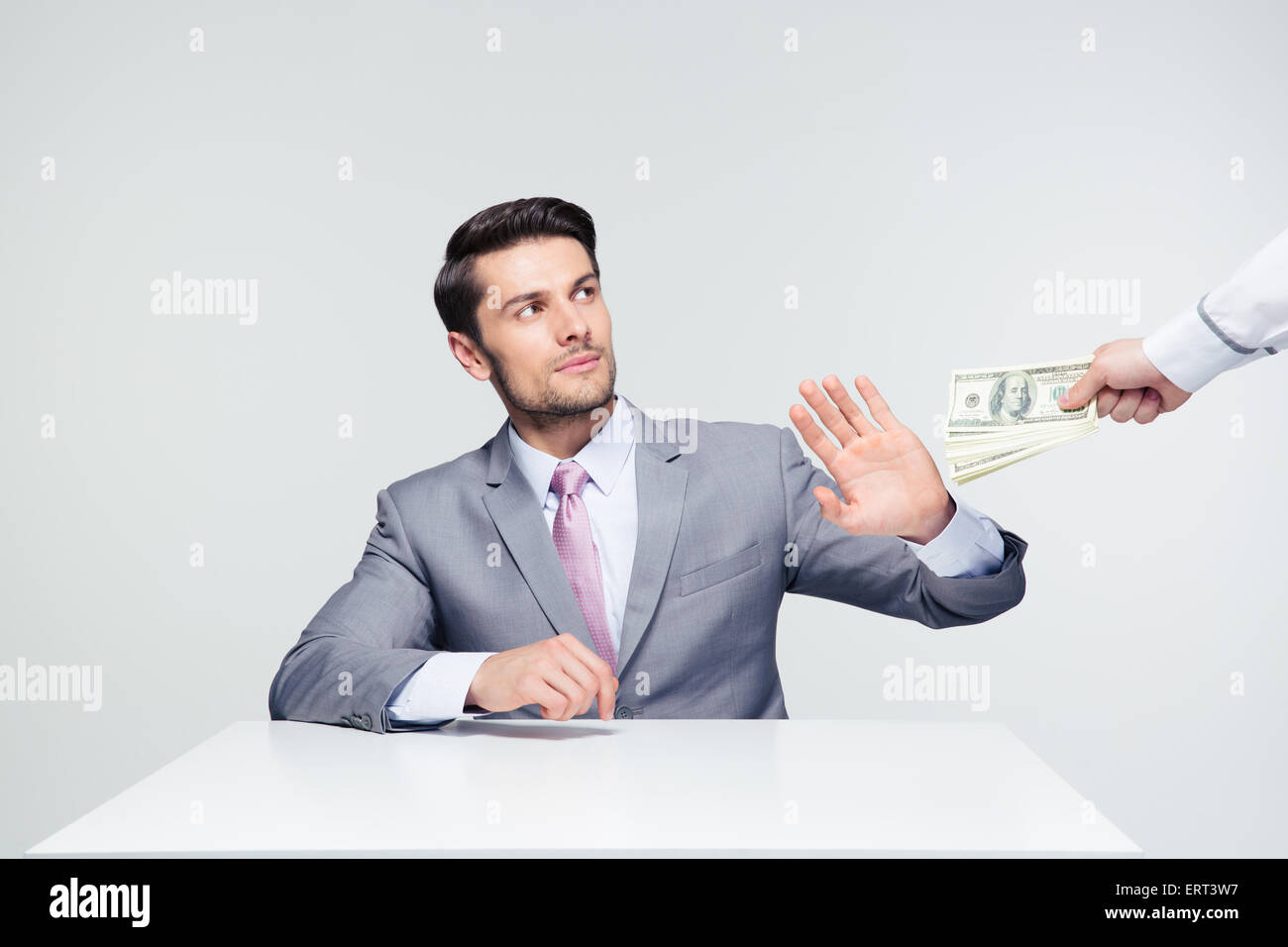 Businessman sitting at the table and gesturing stop sign while someone proposing money to him over gray background - Stock Image