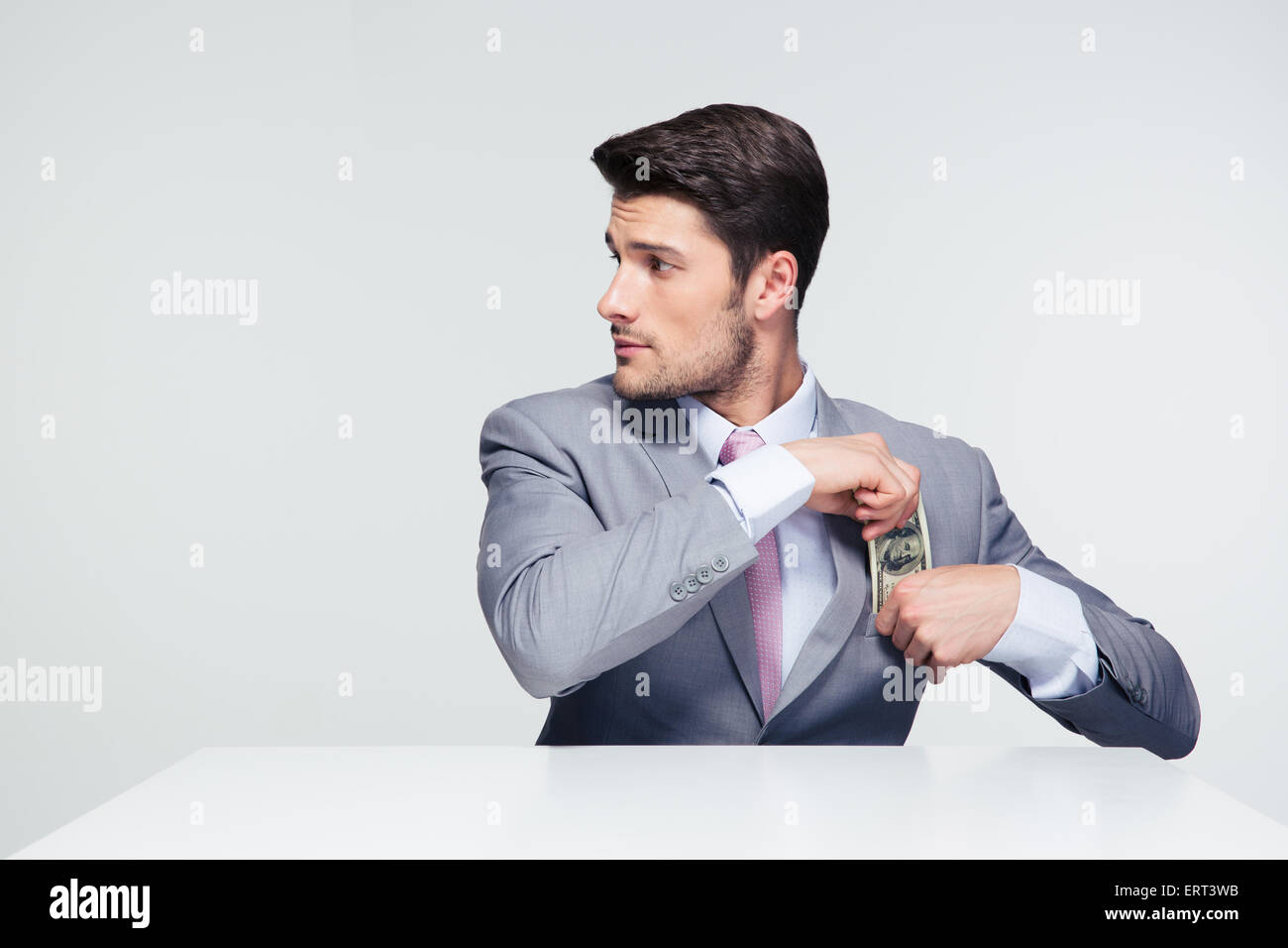 Businessman sitting at the table and putting money in pocket over gray background. Looking away - Stock Image