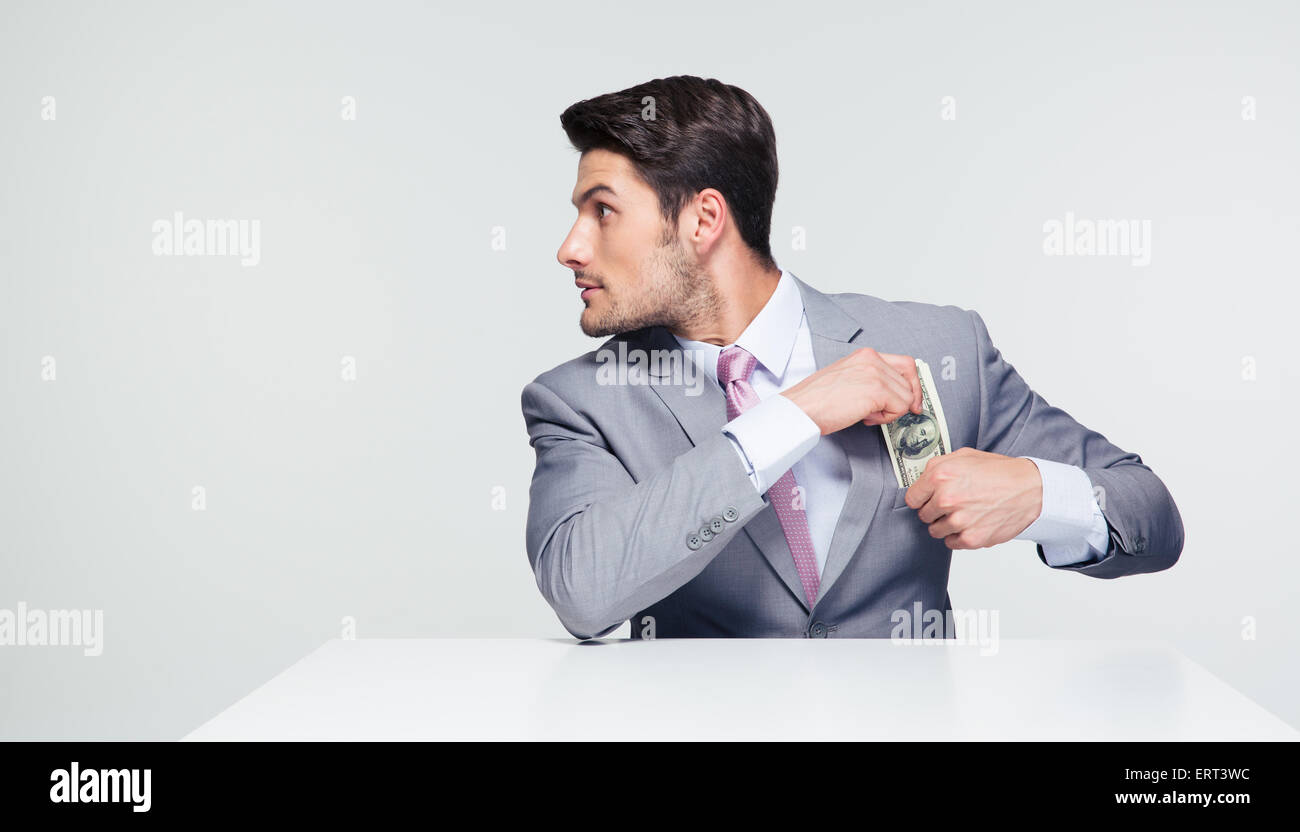 Young businessman sitting at the table and putting money in pocket over gray background. Looking away - Stock Image