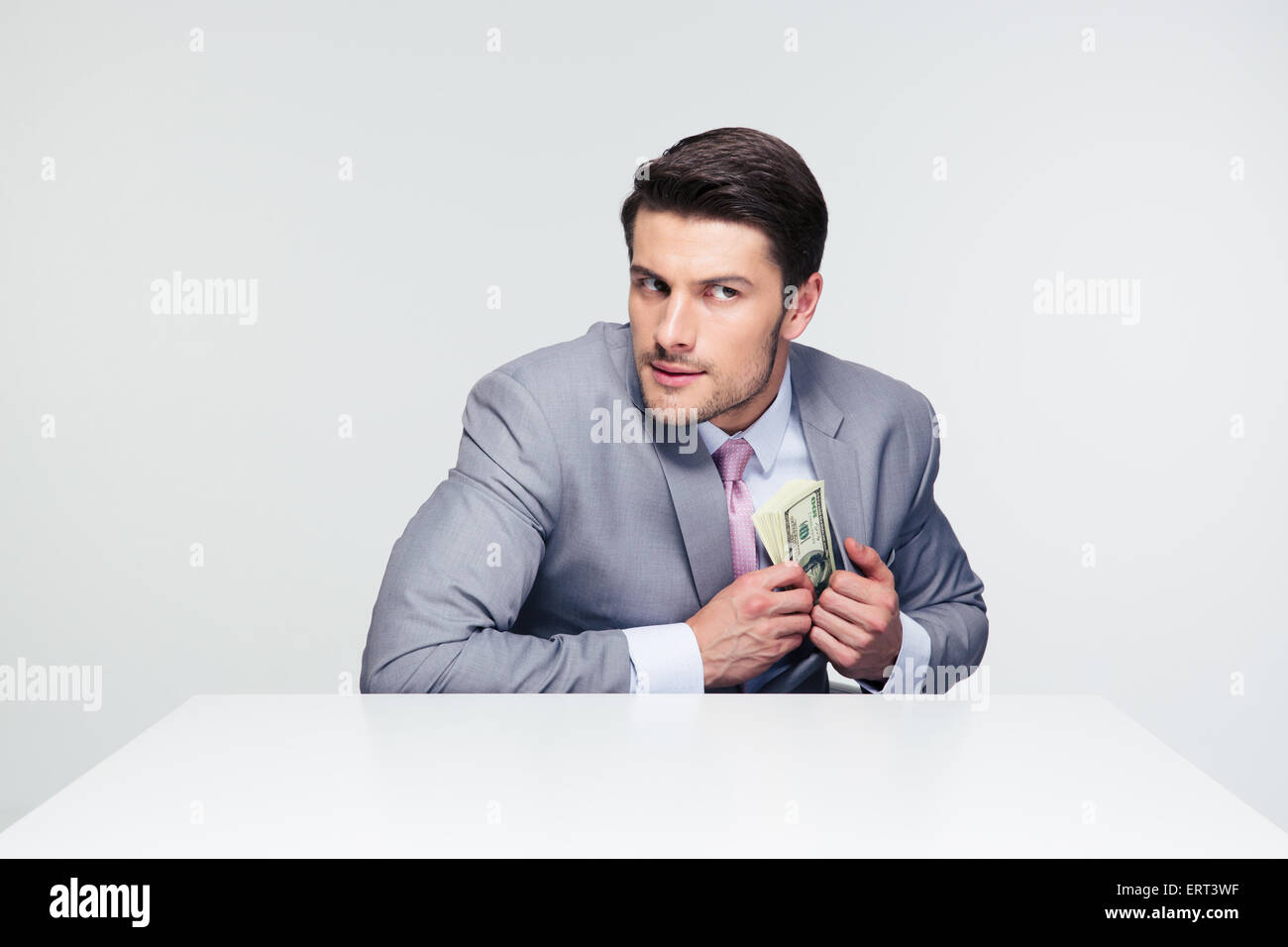 Businessman putting money in pocket over gray background and looking away - Stock Image