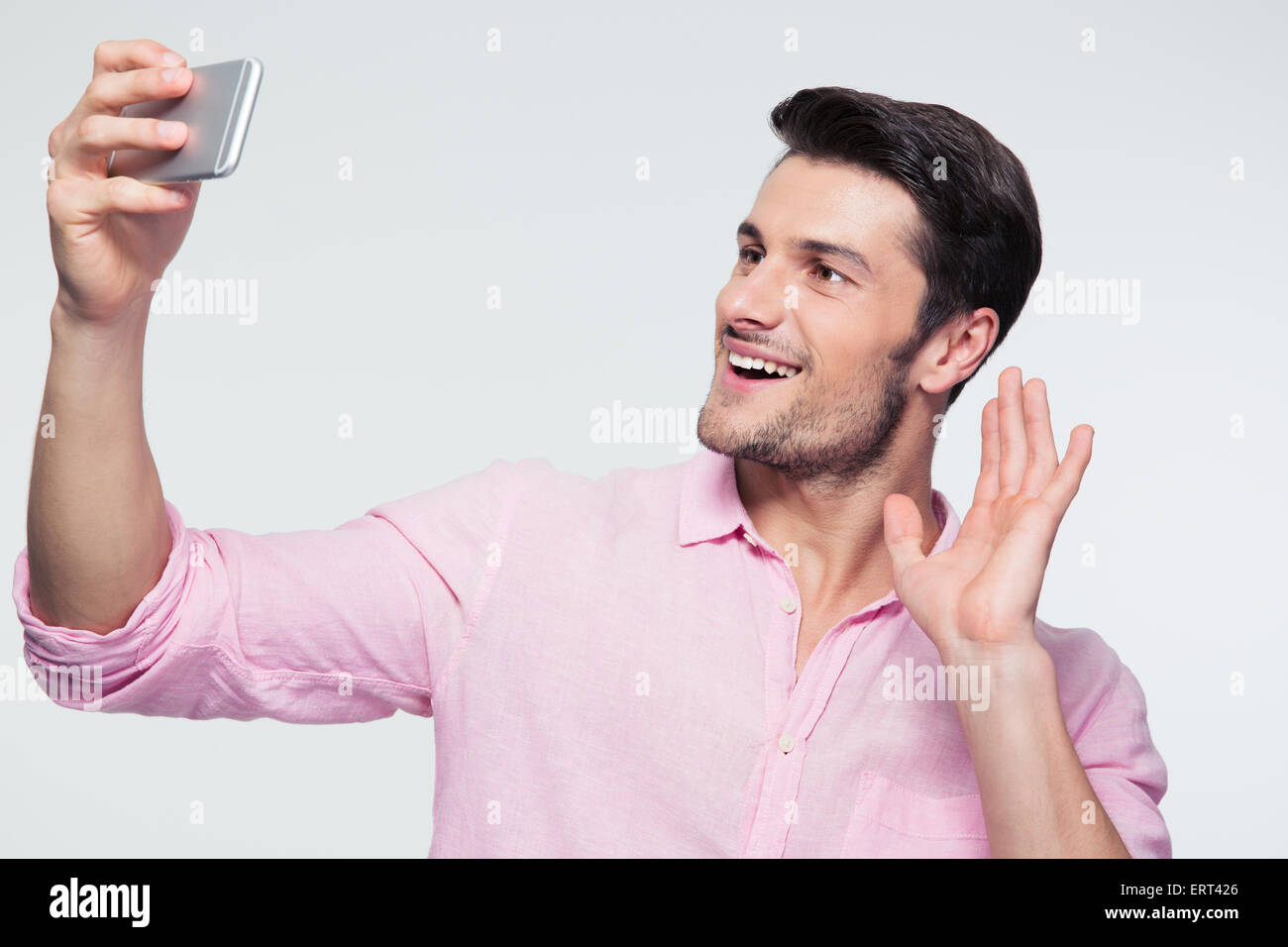 Happy businessman showing greeting sign on smartphone over gray background - Stock Image