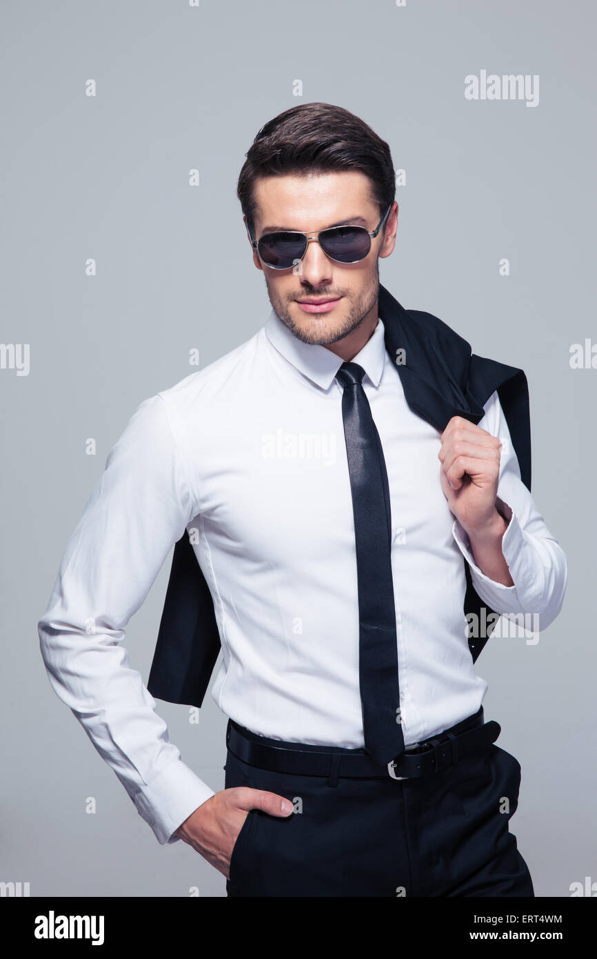 Fashion businessman with jacket on shoulder and sunglasses standing over gray background and looking at camera Stock Photo