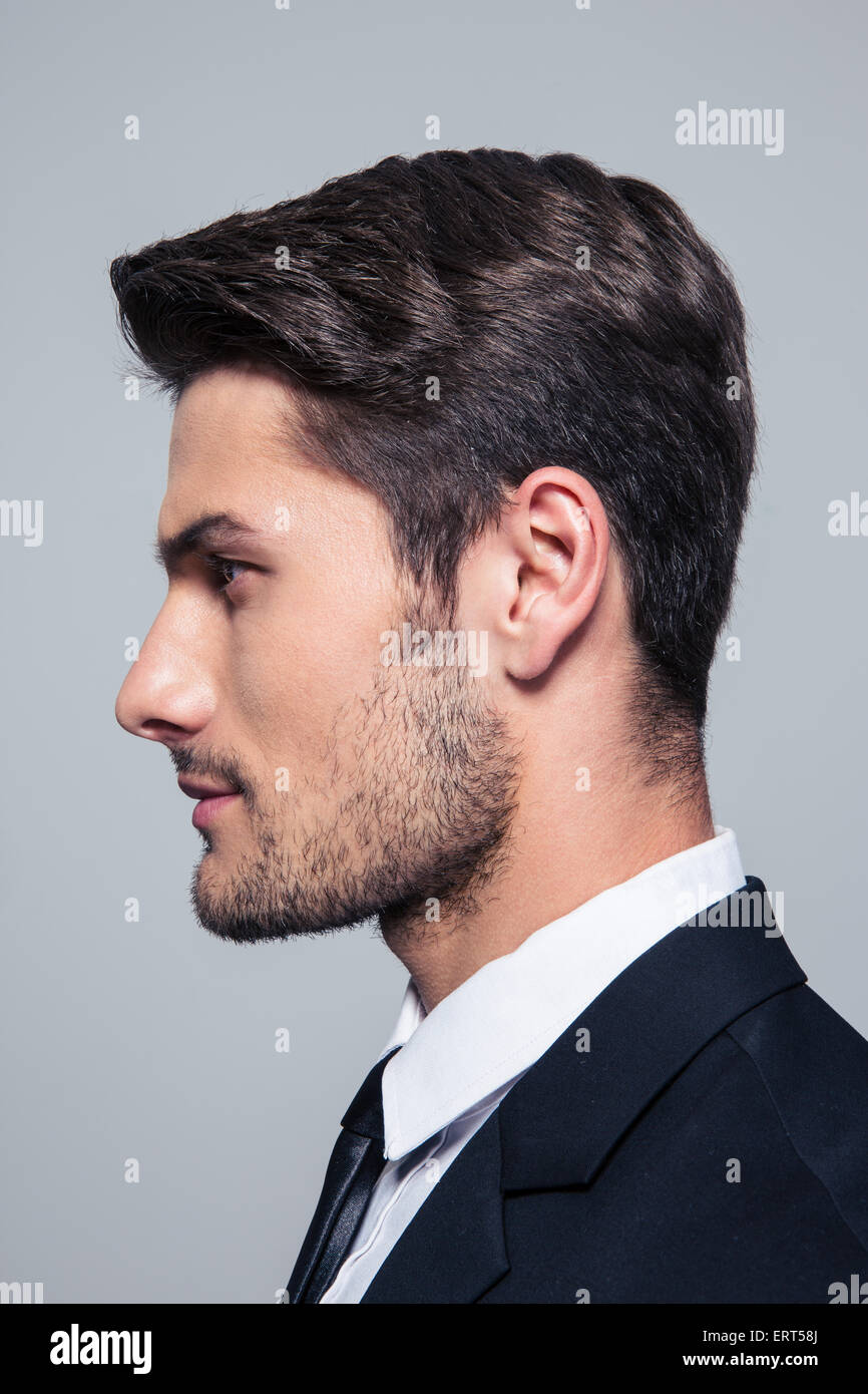 Side view portrait of a handsome businessman over gray background - Stock Image