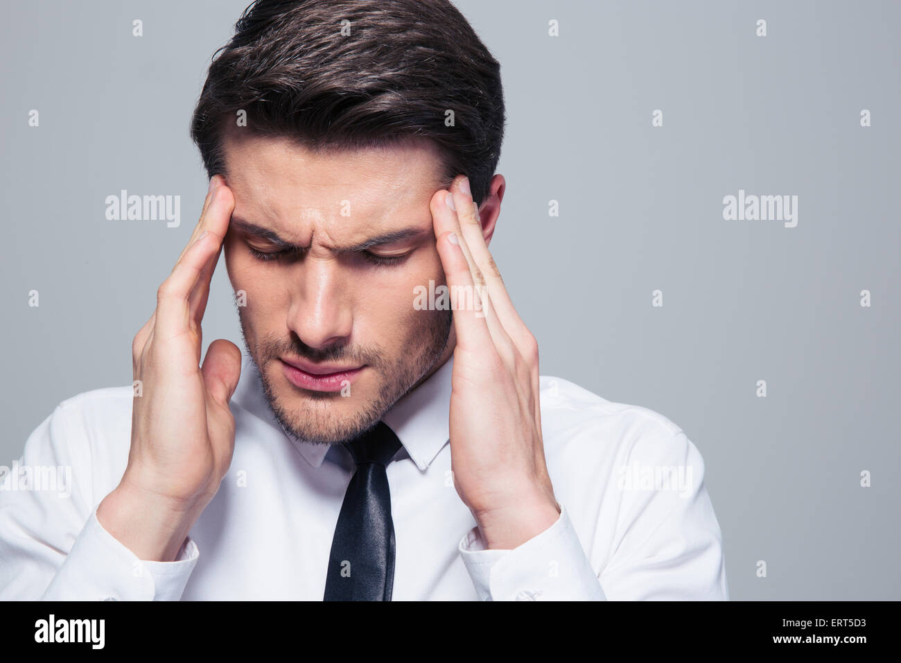 Businessman having headache over gray background - Stock Image