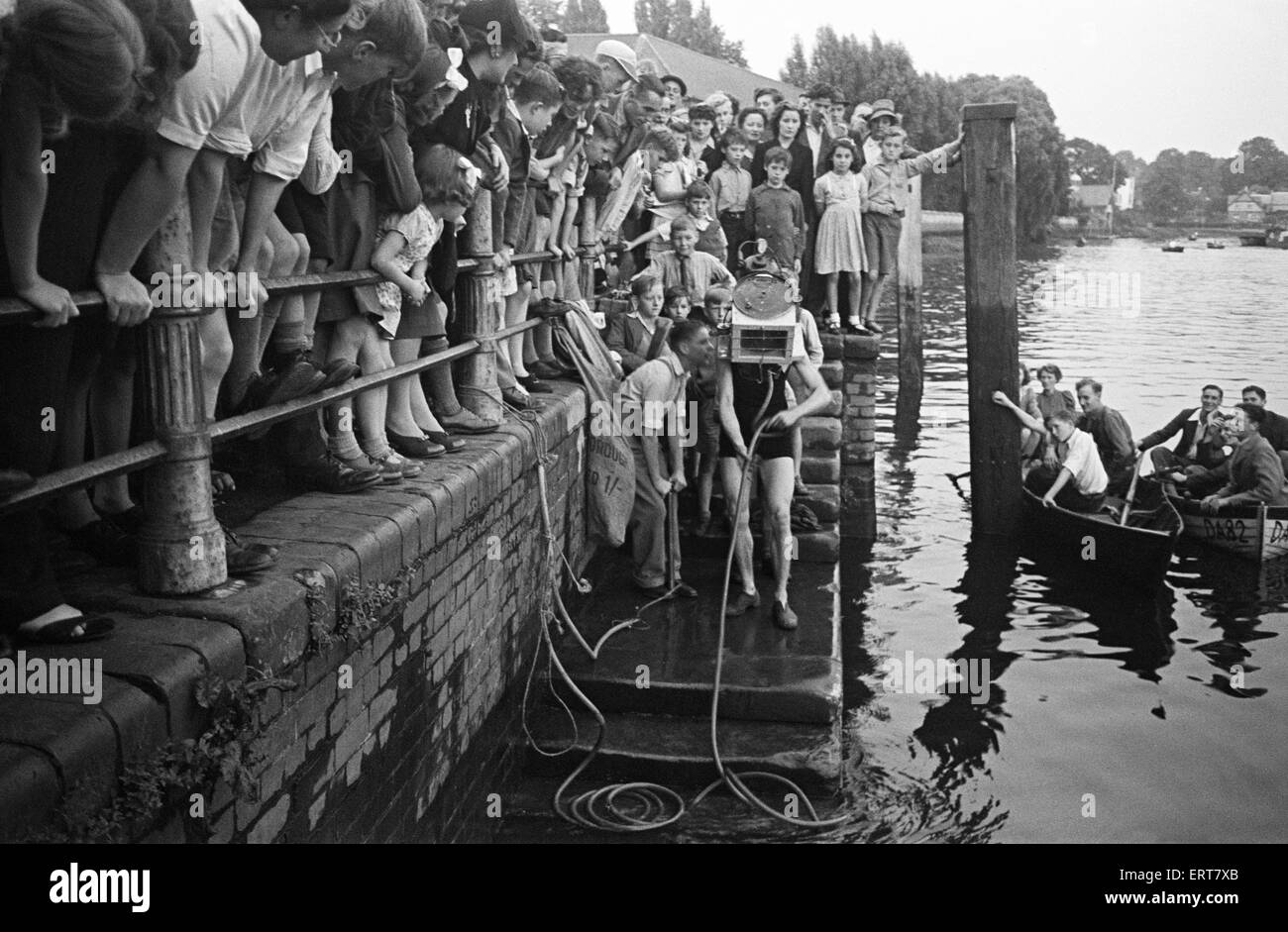 Testing out home made diving equipment, with crowds watching. Wiltshire. Circa 1945. - Stock Image