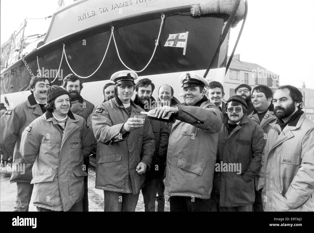 Lifeboat crew at Redcar sharing a drink, with the Sir James Knott Oakley 37 ft Lifeboat in the background. 12th - Stock Image