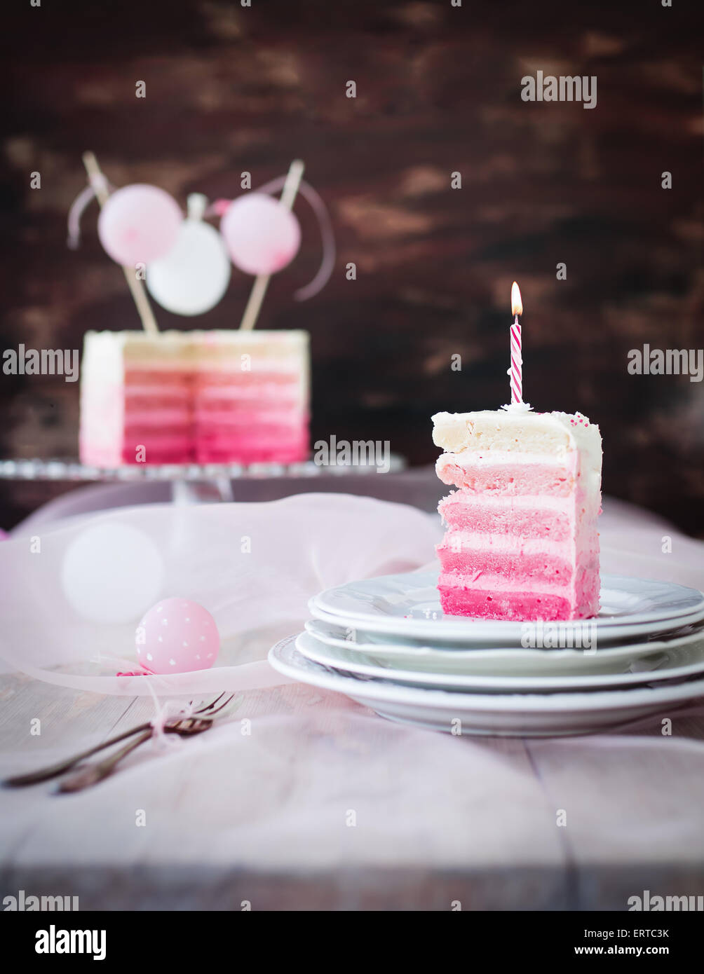 Piece of birthday cake in pink and white. with birthday candle on it. - Stock Image