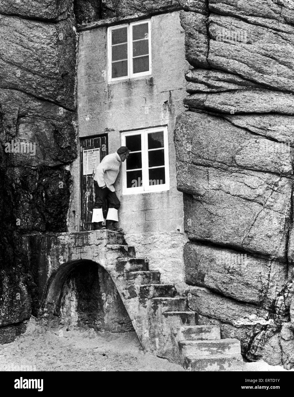 A man looks into the window of a tiny house built into the rocks overlooking the sandy cove of Porthcurno, Cornwall. - Stock Image