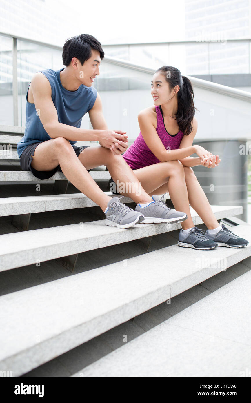 Young couple resting on the stairs after exercise - Stock Image