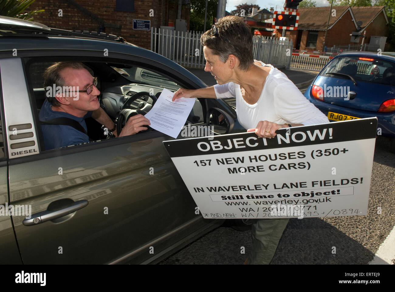 Local resident canvassing a motorist regarding a protest over a proposed new high density housing development which - Stock Image