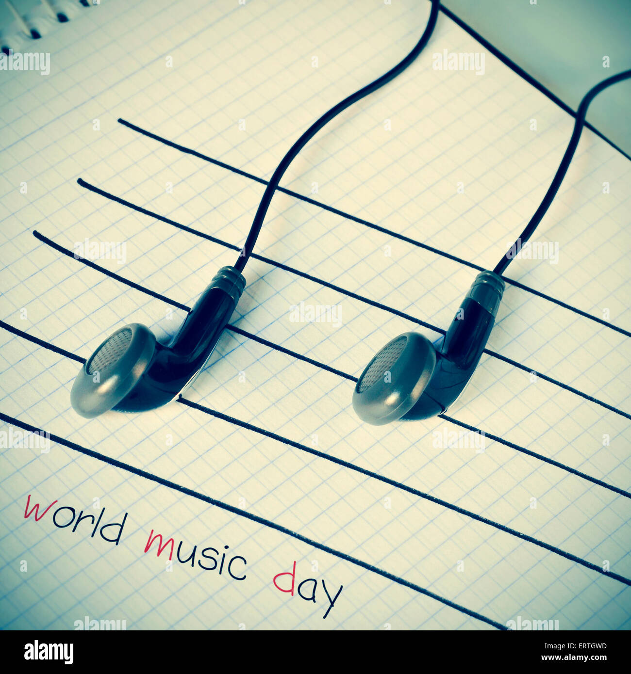 a pair of earphones placed on a staff drawn on a notepad simulating musical notes, and the text world music day - Stock Image