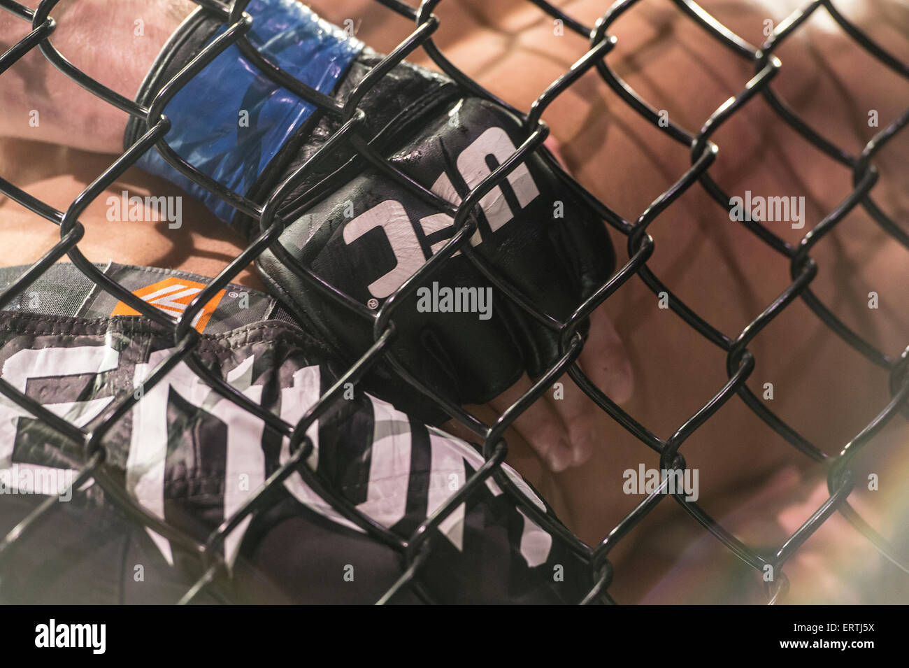 UFC Cage fighters gloves grapple in the ring up against the cage in the Ultimate Fighting Championship mma bout - Stock Image