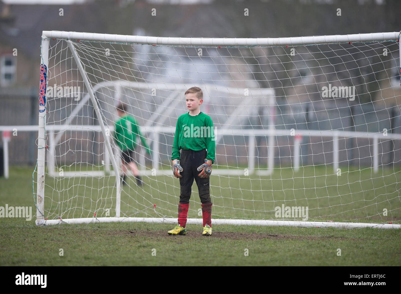 Young boy playing in goal for his football team - Stock Image
