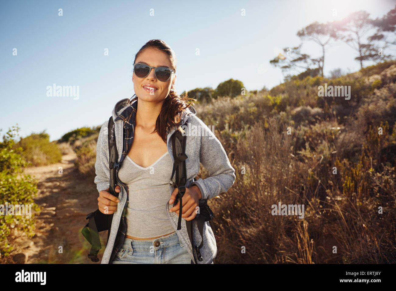Portrait of a beautiful young hiker woman trekking in nature. Young caucasian woman wearing sunglasses looking at - Stock Image