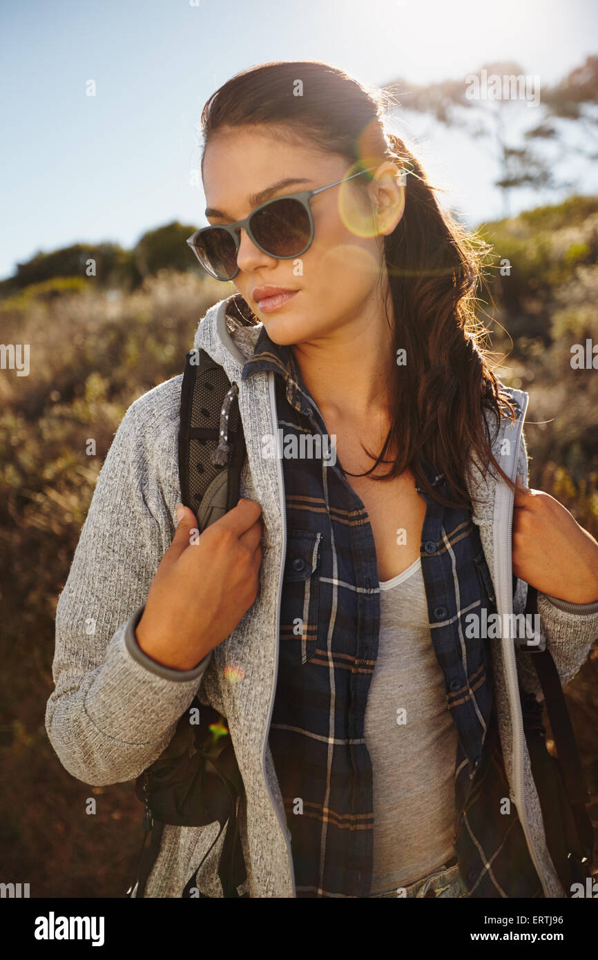 Portrait of an attractive young female hiker in nature. Caucasian young woman wearing sunglasses and carrying a - Stock Image