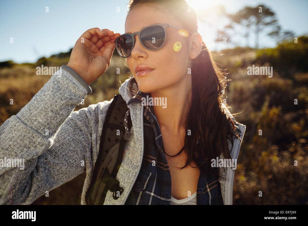 Portrait beautiful young woman hiking on a summer day. Caucasian female wearing sunglasses looking away, outdoors - Stock Image