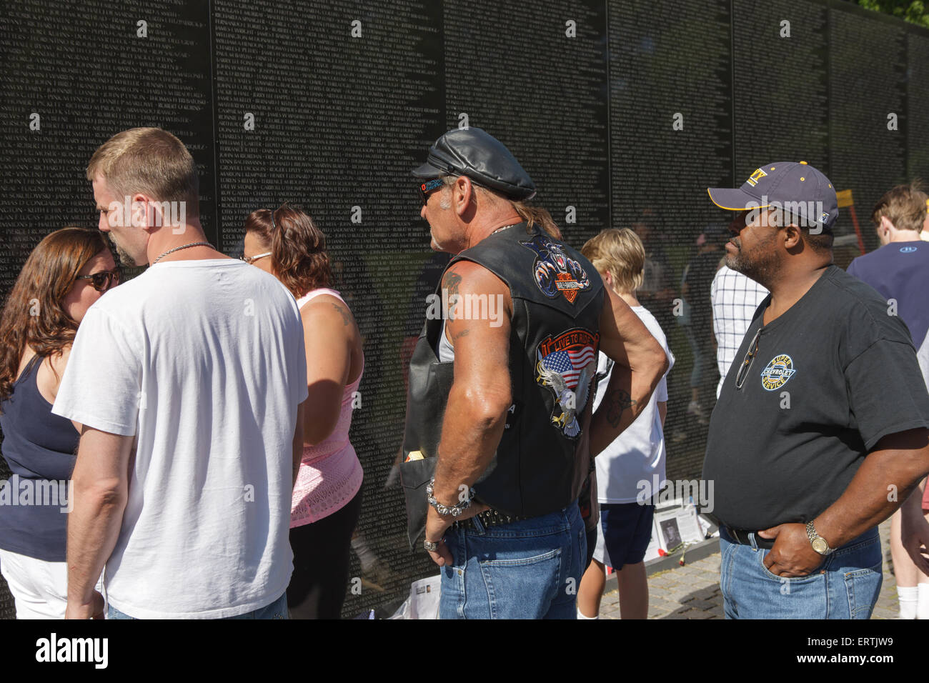 Visitors reflect while viewing names on the Vietnam Veterans Memorial in Washington, DC. - Stock Image