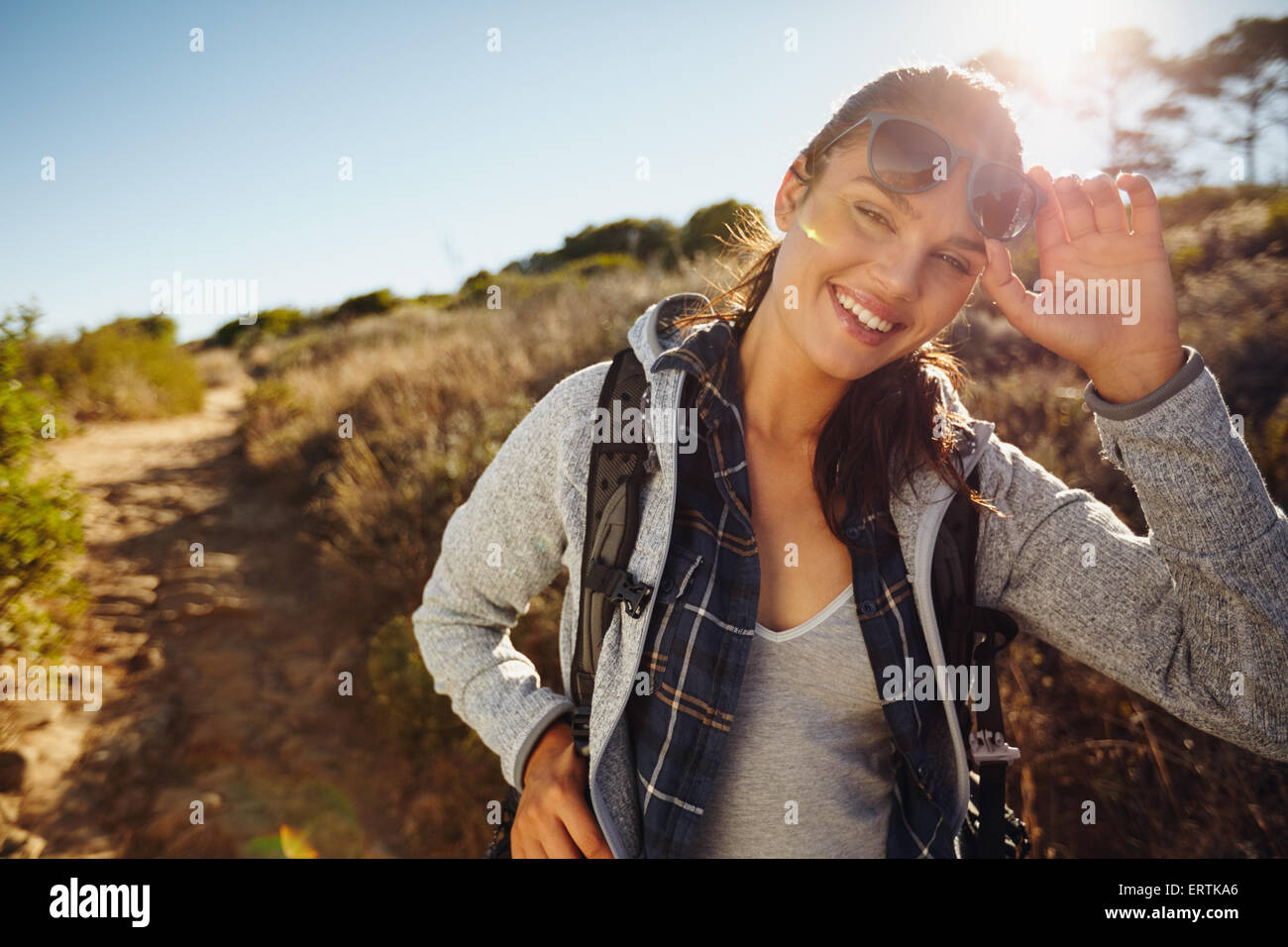 Portrait of a happy young hiker woman in nature. Young caucasian woman wearing sunglasses looking at camera with - Stock Image