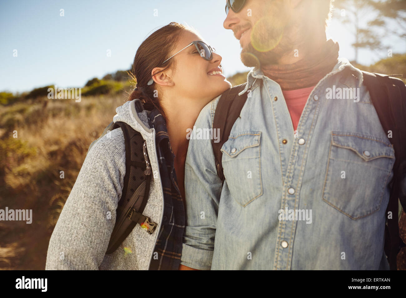 Love couple looking at each other smiling, hiking in nature. Young caucasian couple on hike on sunny day. - Stock Image