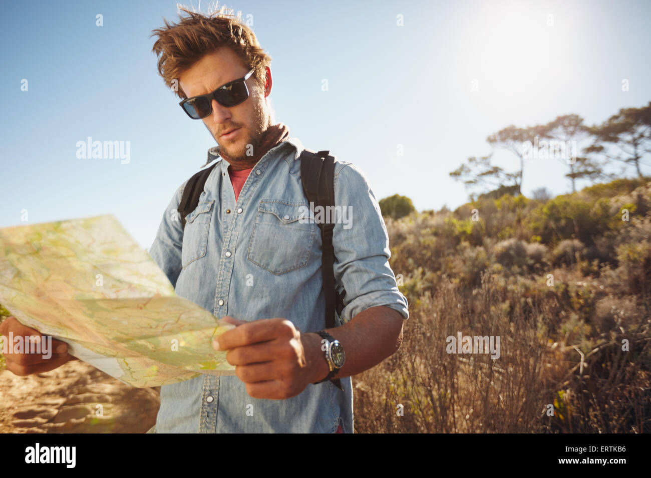 Shot of a handsome hiker using a map. Hiker using a map to navigate his hike on a summer day. - Stock Image