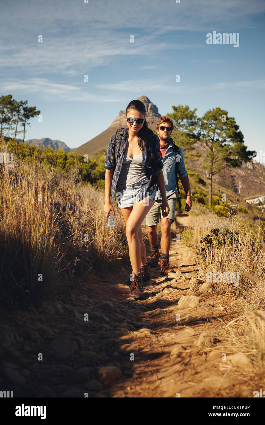 Young couple trekking together, summer vacation in countryside during a sunny day. Caucasian hiker couple walking - Stock Image