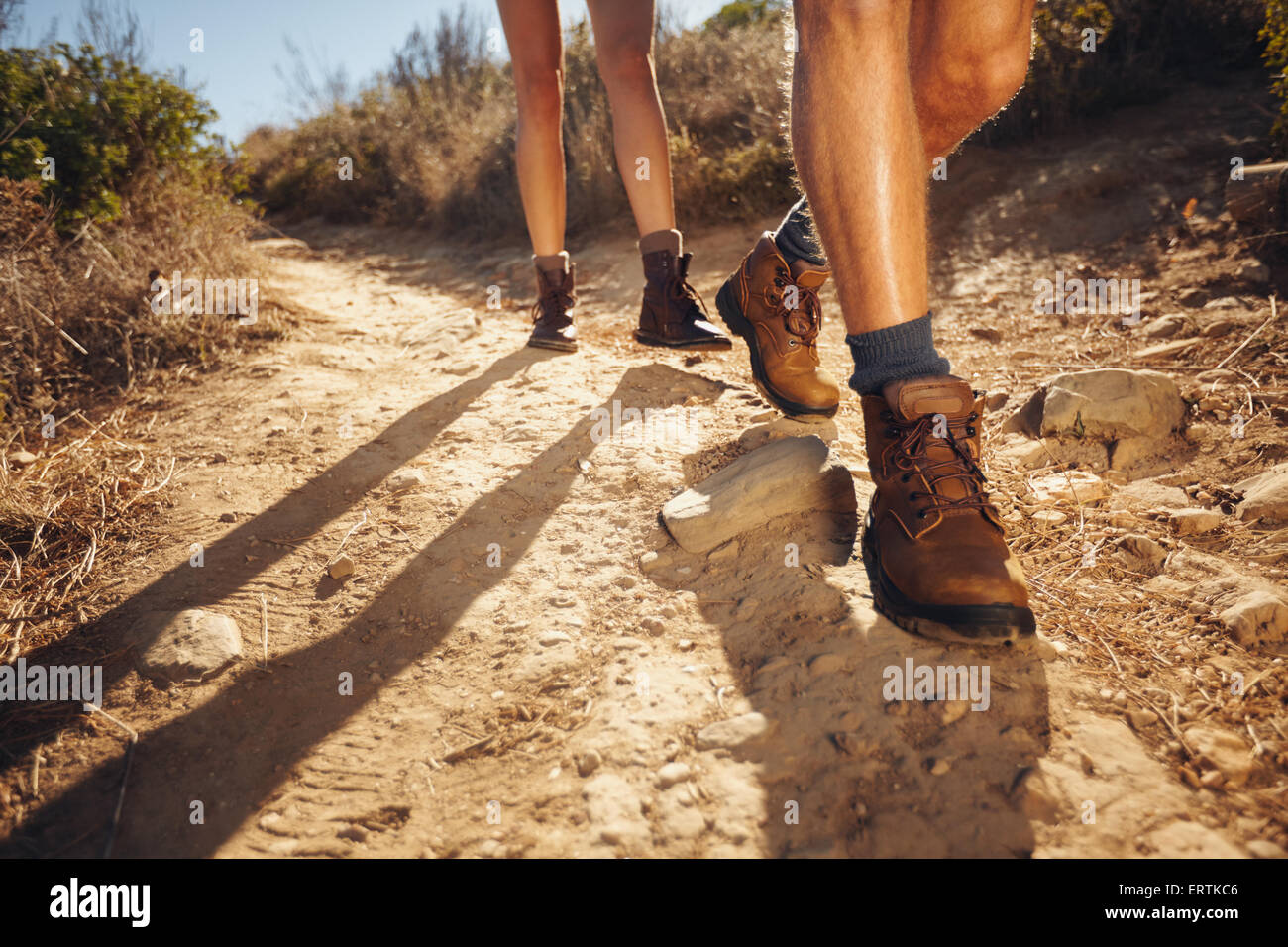 Close-up of legs of young hikers walking on the country path. Young couple trail waking. Focus on hiking shoes. - Stock Image